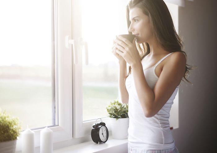 Guten Morgen Bilder - ein Mädchen genießt Kaffee und sieht durch das Fenster