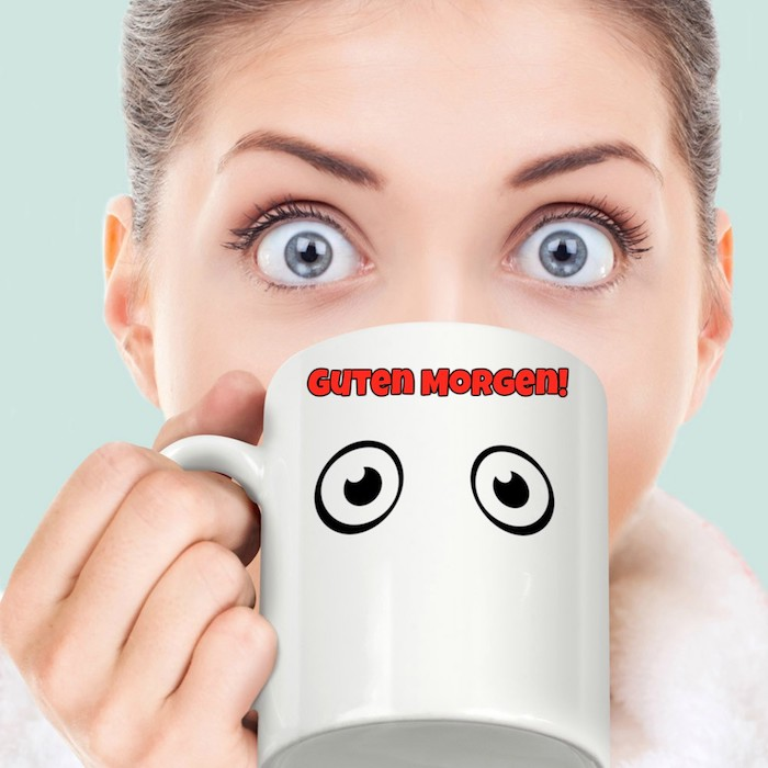 ein Kaffeebecher mit zwei großen Augen gemalt und eine junge Dame mit großen blauen Augen