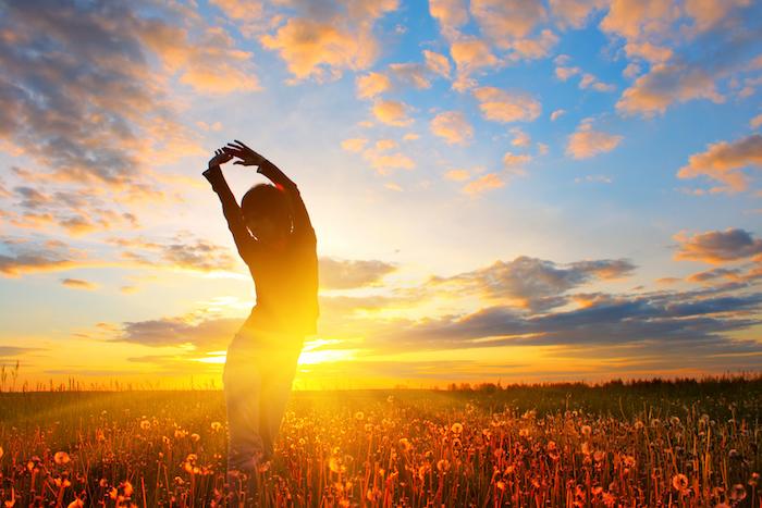 ein Mensch turnt am Tagesanbruch auf einer Wiese mit Pusteblumen - Guten Morgen Bilder