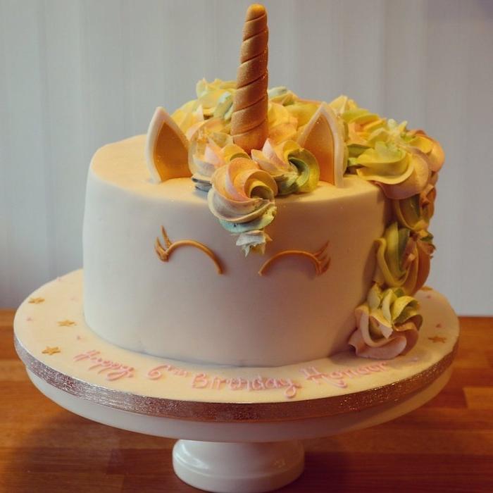 idee zum thema einhorn kuchen dekof und einhorn torte - hoier ist eine weiße einhorn torte mit einem weißen einhorn mit einem goldenen kleinen gelben horn und mit einer gelben mähne aus sahne