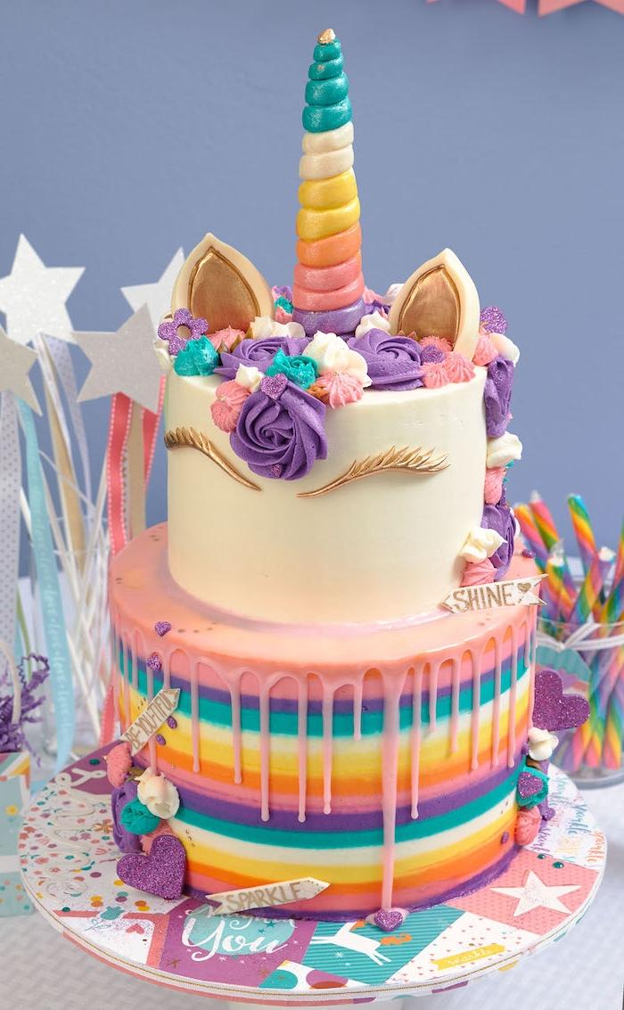 idee für eine zweistöckige einhorn torte mit einem weißen horn mit einem langen regenbogenfarbenen horn und mit einer mähne aus lila und kleinen blauen und pinken rosen - idee für einhorn kuchen deko