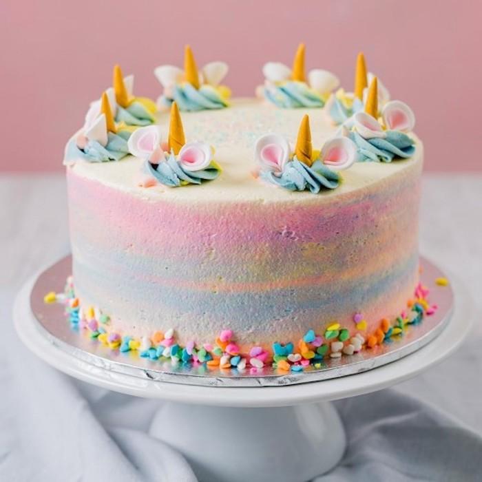 noch eine regenbogenfarbene einhorn torte mit kleinen einhörnern und mit jleinen gelben hörnern und ohren - idee für einhprn kuchen rezept