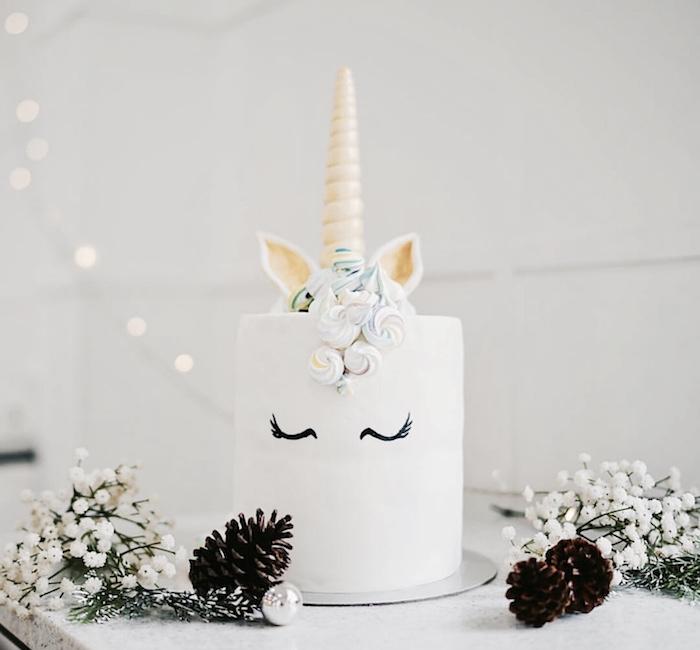idee für eine weiße einhorn torte mit einem einhorn mit schwarzen augen und mit einem gelben goldenen horn und mit einer weißen mähne aus sahne
