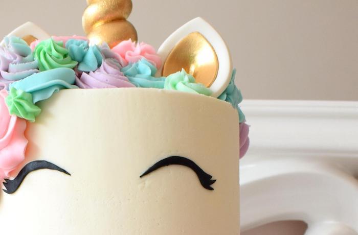 hier ist eine weiße einhorn torte mit schwarzen augen und mit einer bunten mähne und mir einem langen bunten horn und mit schwarzen augen - idee für einhorn kuchen
