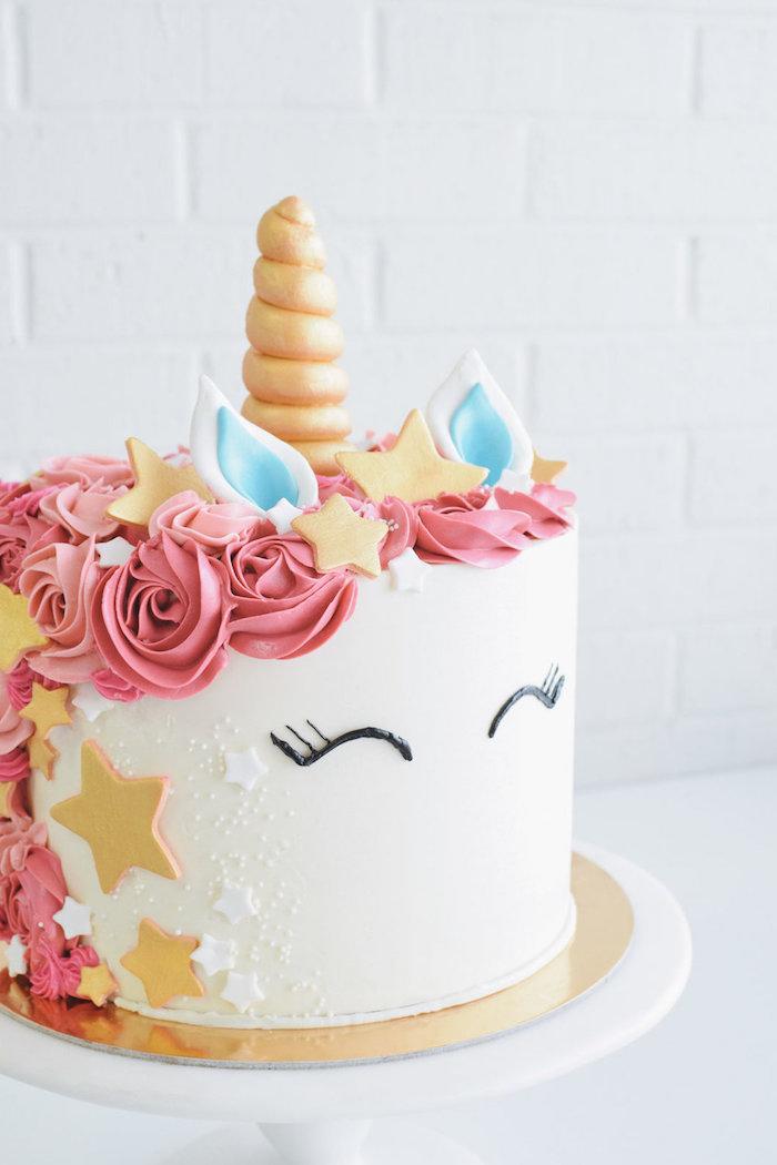 eine torte mit einem weißen einhorn mit gelben sternen, einer pinken mähne aus sahne, pinken rosen, kleinen blauen ohren und einem goldenen horn und schwarzen augen