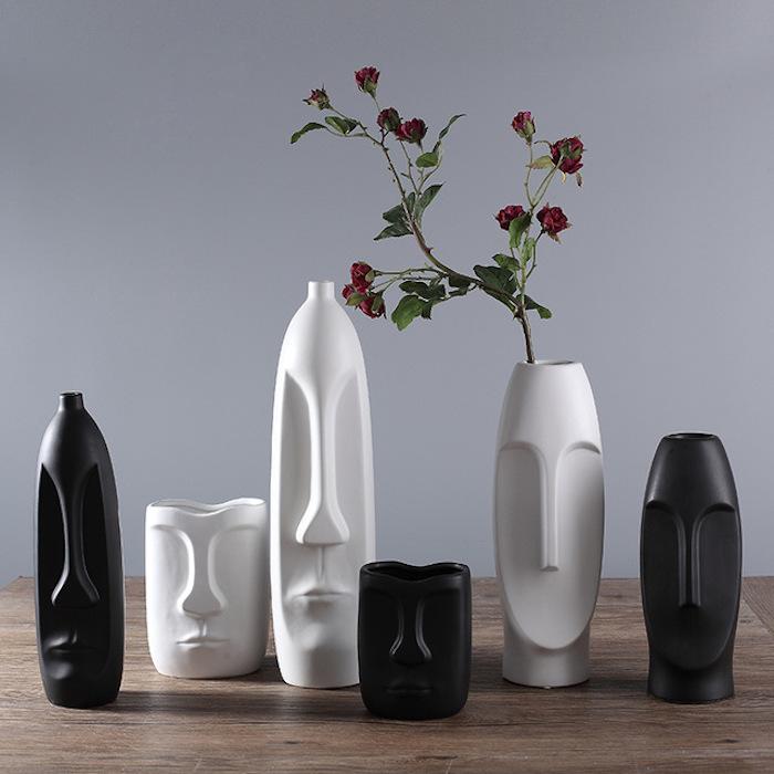 Geschenke zur Einweihung: sechs dekorative Vasen mit skandinavischem Design, die Gesichtsskulpturen ähneln, drei weiße und drei schwarze Blumenvasen in verschiedenen Größen, Holztisch mit Lacküberzug, hellgraue Wand als Hintergrund, rote Nelken in einer Blumenvase