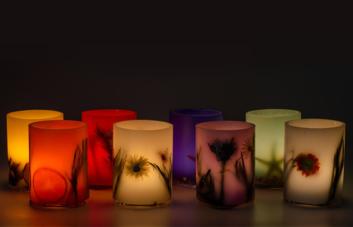 acht Kerzenleuchter aus mattem farbigem Glas mit Pflanzenmotiven, Kerzenleuchter in verschiedenen Farben, brennende Kerzen vor einer schwarzen Hintergrund
