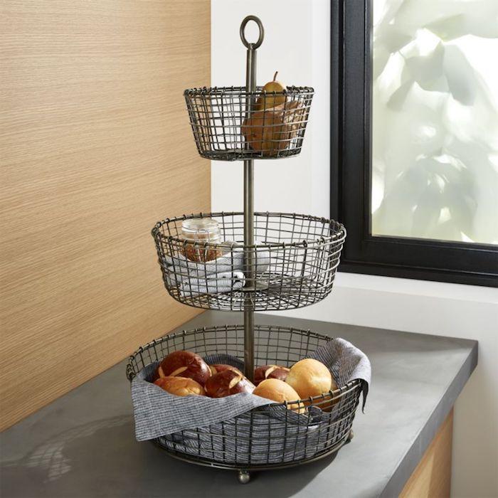 Obst- und Gemüseständer aus Metall für die heimliche Küche, Obstständer mit drei Körben aus Metall, Gemüseständer mit Kartoffeln und Zwiebeln, mit einem Einmachglas und zwei Birnen, Küche mit Rückwand aus Holzpaneelen, Fenster aus mattem Glas, das zum Garten schaut