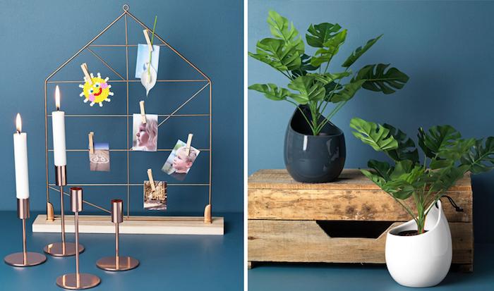 metaller Rahmen in der Form eines Hauses zum Aufhängen von Fotos mit Klammern, Fotoständer mit mit einem Holzbrett, ein Satz Kerzenleuchter mit Kupferabdeckung, zwei lange weiße Kerzen, ein dunkelgrauer und ein weißer Blumentopf, kleine Holzkiste mit einer Schublade, blau-graue Wand