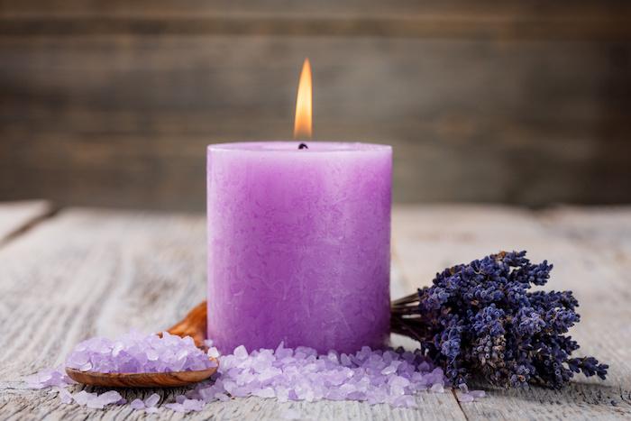 Aromatherapie unter der Dusche, brennende Dufkerzen mit Lavendelaroma und einer orangen Flamme, großer Esslöffel aus Holz, Badewanne-Salz mit Lavendelduft, ein Strauß getrockneter Lavendel, Badezimmer mit Holzwanden
