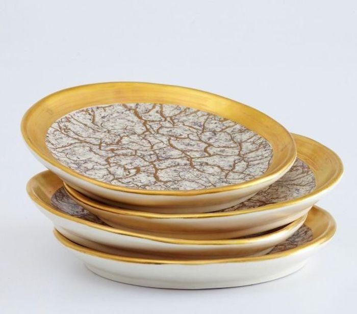 vier runde Teller mit vergoldeten Kanten und marmorähnlicher Verzierung, Tellersatz aus vier Serviertellern mit Verzierungen in Goldfarbe, Bild mit weiß-grauer Hintergrund
