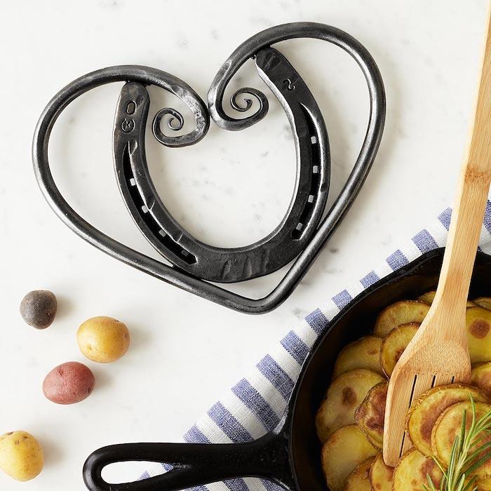 Topfuntersetzer aus Edelstahl in der Form eines Herzens und eines Hufeisens, Topf-Untersetzer mit kleinen Löchern für heiße Töpfe, vier kleine runde Kartoffeln aus verschiedenen Sorten, gebratene Kartoffeln in Scheiben in einer schwarzen Bratpfanne mit großem Henkel, gestellt auf einen Tuch mit Streifenmuster, Kochspachtel aus Holz mit kleinen Löchern