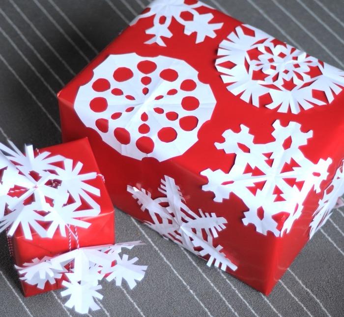 Bastelideen Winter - rote Verpackungen mit weißen Schneeflocken verziert zu Geschenken