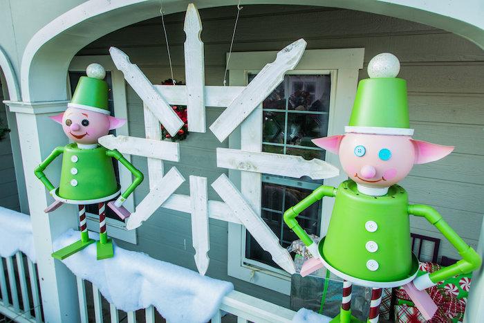 zwei grüne Elfen aus Gartenmaterialien selbstgebastelt, eine Schneeflocke aus Holz in der Mitte - Bastelideen Winter
