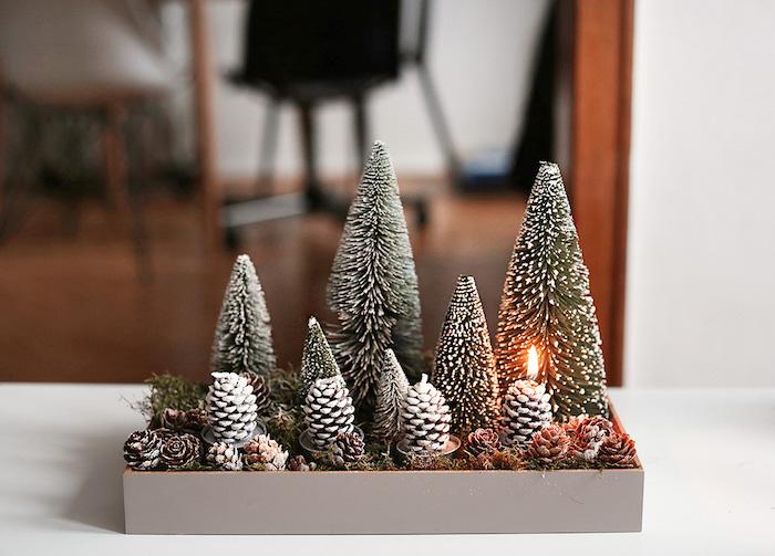 kleine bäume mit schnee und kleine braunen zapfen mit schnee und feuer - idee für einen adventskranz - adventskranz selber machen