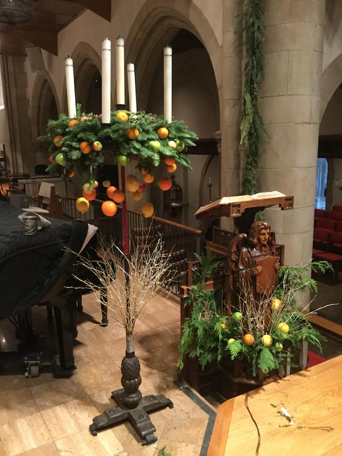 adventskranz midern - ein adventskranz mit ästen mit grünen blättern und orangen früchten und fünf langen kerzen
