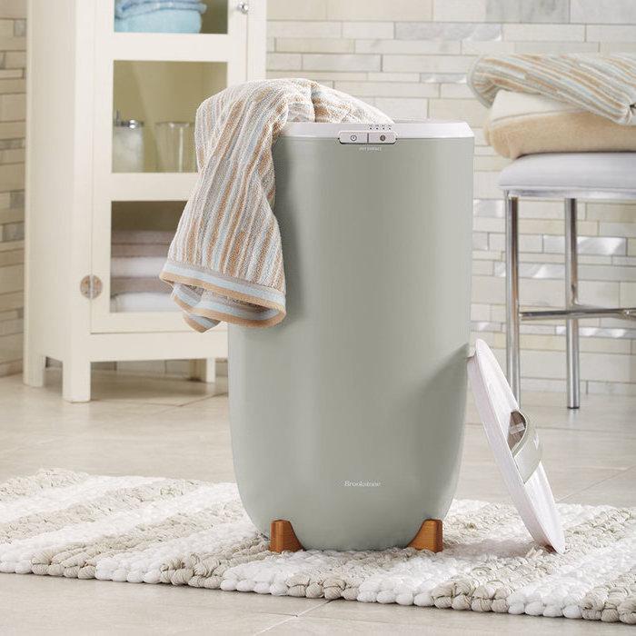 Bad- und Handtuchwärmer in einem luxuriösen Badewanne mit cremeweißen Wand- und Bodenfliesen, cremeweißer Badeschrank mit runder Metallgriff und Glastür, Badezimmerschrank mit drei Regalen und vier kurzen Beinen, Luxus-Badezimmer mit einem weißen Lederstuhl mit Metallbeinen, weicher Flechtteppich mit weißen und beigen Streifen