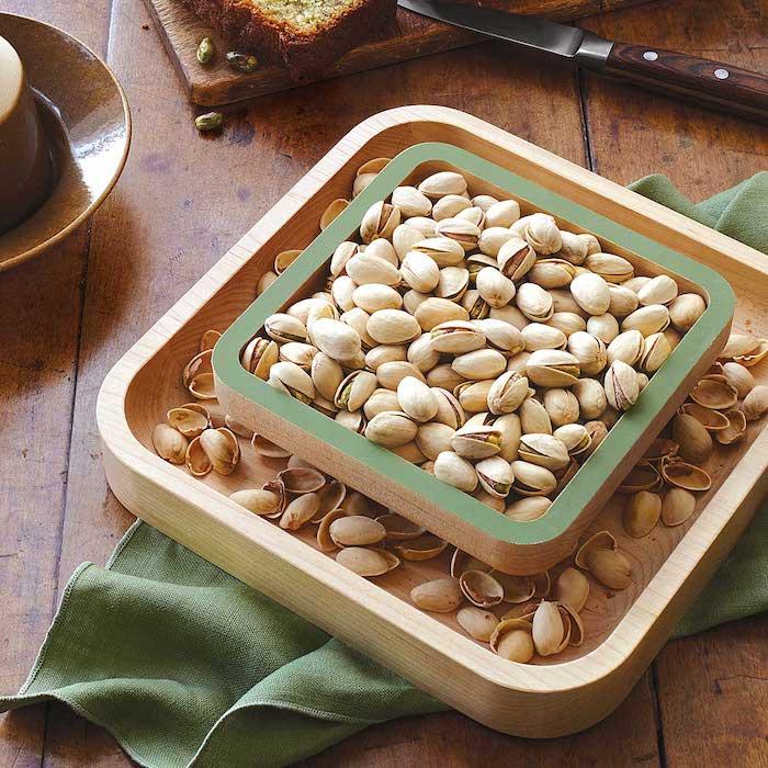 Nusssch[ssel aus Holy in viereckiger Form mit stumpfen Ecken und zwei Fächern - ein Fach für die Nüsse und ein Fach für die Schalen, Pistazien mit Schalen in einer quadratischen Holzschüssel mit grünen Kanten, eine Olivengrüne Stoffserviette auf einem alten Holztisch, Schneidebrett aus Holz mit einer Brotscheibe, Buttermesser aus Edelstahl mit Henkel aus Holz, ein dunkelbrauner Teller mit Glanzüberzug