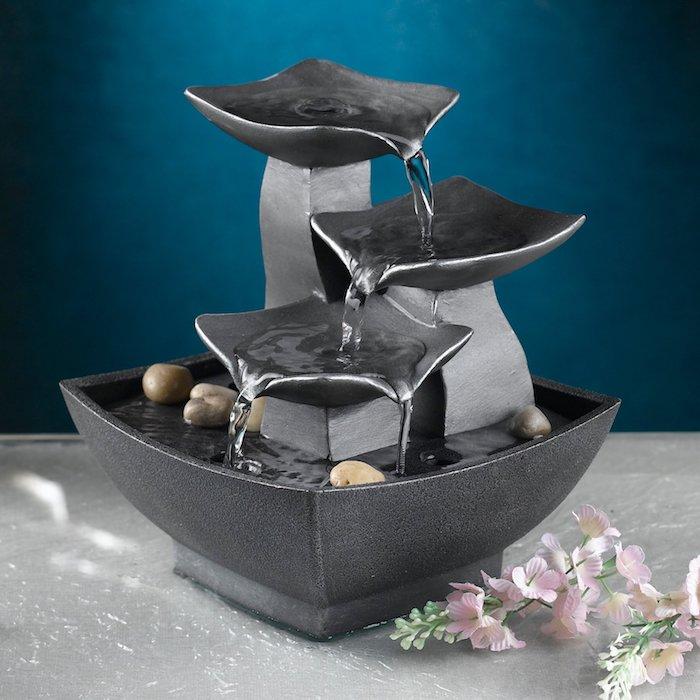 kleine dekorative Tischbrunne in Dunkelgrau mit drei kleinen Wasserfällen und ein paar kleinen Flußsteinen in Beige, weißer Tisch mit Glastischplatte, kleine frische Baumblüte mit Rosafarbe, Wand in dunkelblauer Farbe