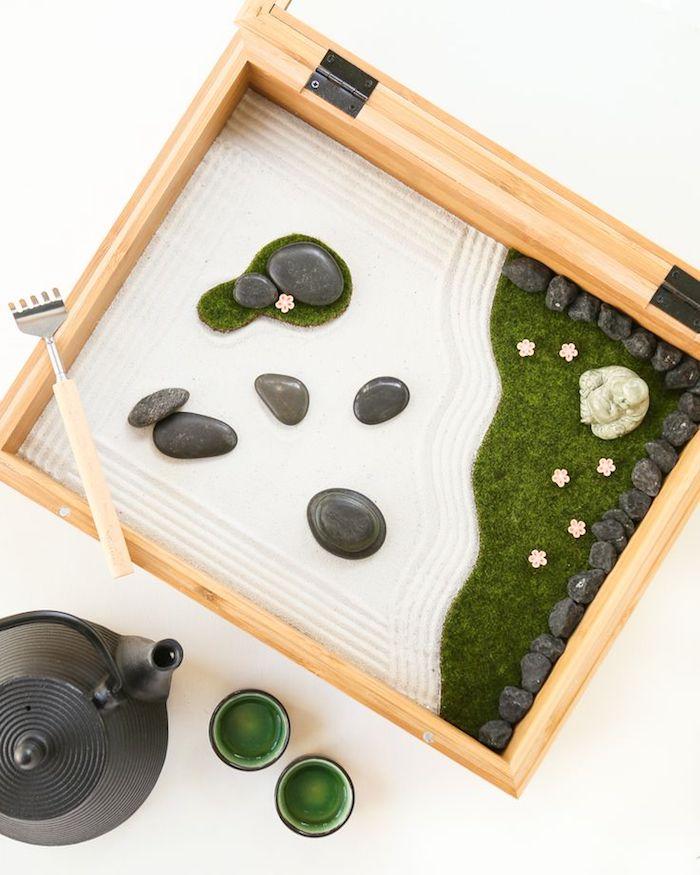 ein Holzkasten mit weißem Sand und kleinen grauen gerundeten Flußsteinen, eine Minifigur von Buddha aus Nephritis, kleiner Zengarten in einer hölzernen Kiste, ein Tee-Set aus schwarzer Teekanne und zwei kleinen Tässchen mit grünen Wänden