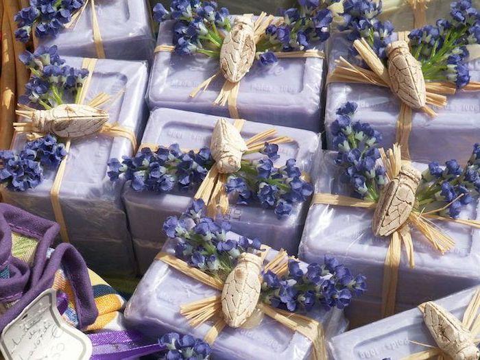 DIY Badeseifen mit ätherischem Lavendelöl und zartem Lavendelduft für weiche Haut, Lavendelseifen in transparenter Zellophanverpackung, ein dekoratives Band mit einem Dekoelement aus Holz, eine lila Kiste mit einem Preisetikett