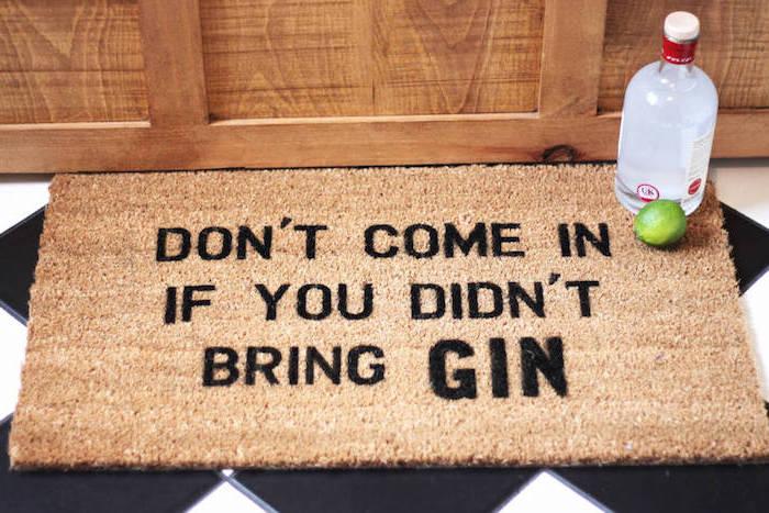 Eingangsmatte in Beige mit einem Spruch auf Englisch mit schwarzen Buchstaben, Boden mit schwarzen und weißen Rhombus-Fliesen, Flur mit Wandverkleidung aus Holz, eine Flasche Gin mit einer Limette daneben