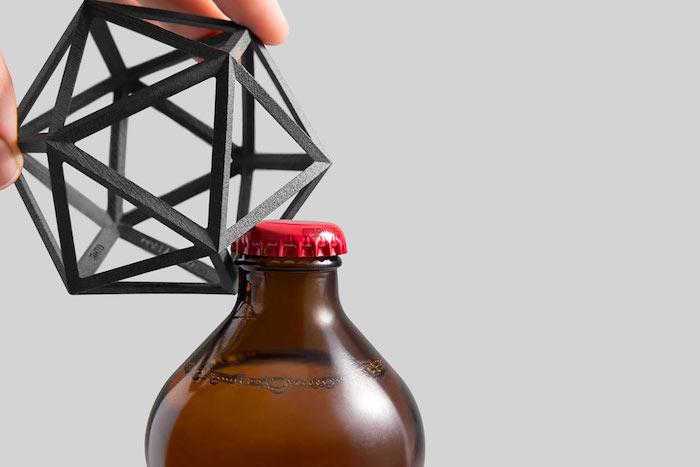 Designer Flaschenöffner aus Edelstahl in der Form eines Vieleckes, eine Bierflasche aus braunem Glas mit rotem Deckel aus Metall, ein Mann öffnet eine Bierflasche