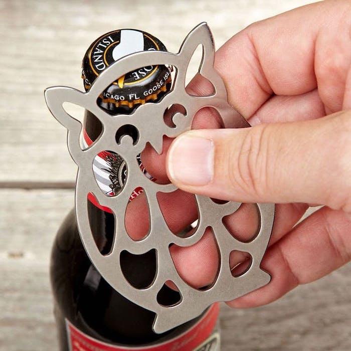 dunkle Bierflasche mit rotem Etikett, schwarzer Metalldeckel mit weißen Buchstaben und goldenem Kant, Bieröffner in der Form einer Eule, Mann mit Bieröffner in der rechten Hand