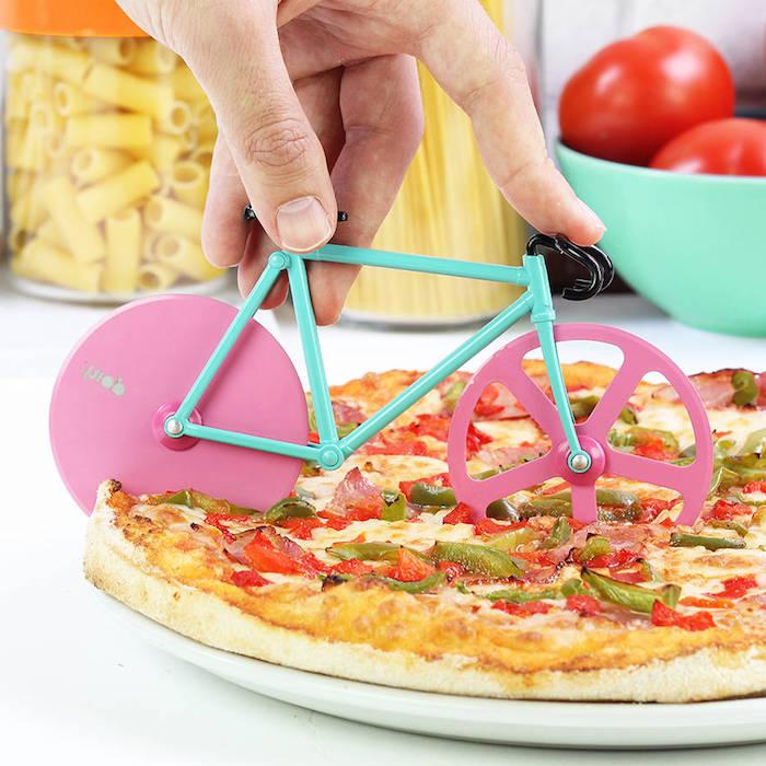 Fahrrad-Pizzamesser mit zwei Schneiden, Fahrrad mit pinken Rädern und türkisblauem Fahrradrahmen, Fahrrad mit schwarzem Fahrradlenker, Plastik-Einmachglas für Pasrta mit orangem Deckel, Spaghetti-Behälter aus Plastik, türkisblaue Schüssel mit zwei roten Tomaten, Pizza-Vegetariana in einem weißen Teller, Pizza mit grünen und roten Paprika