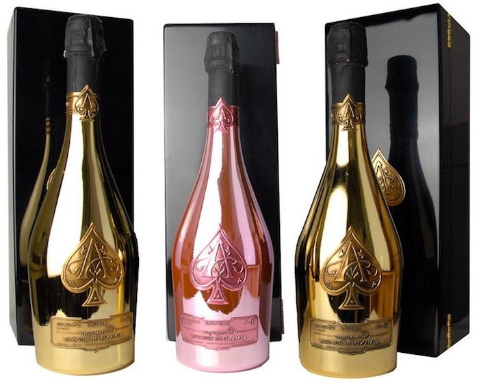 drei Champagnenflaschen mit Premium-Verpackungen in Goldfarbe und Rosa jeweils mit einem Pik, drei schwarze Kisten für Champagneflaschen