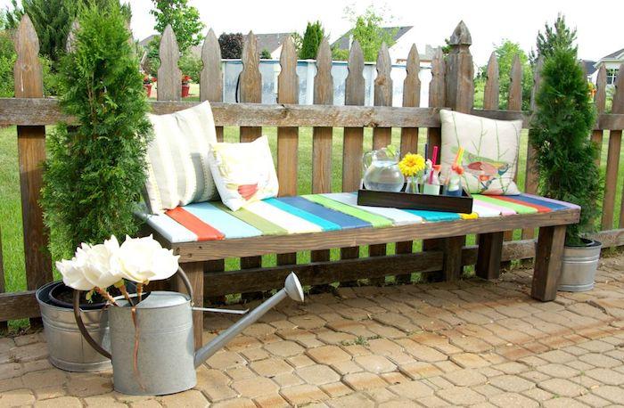 gartengestaltung bilder - eine gartenbank aus holz mit drei weißen kissen - garten und weiße blumen und gartentor