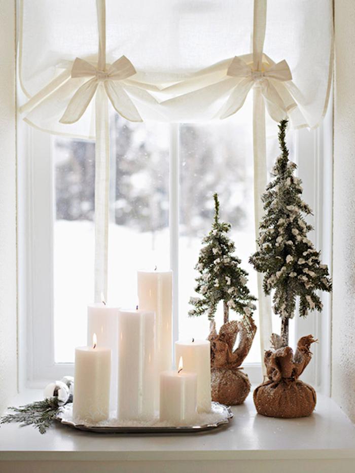 weihnachtsdeko auf einem kleinen kaffeetisch unter dem fenster weiße kerzen in verschiedenen größen vorhänge deko mit schleifen