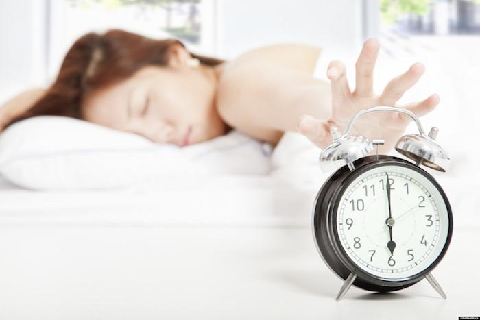 ein vintage Wecker im Vordergrund, die junge Dame in der Hintergrund will sich nicht aufwecken