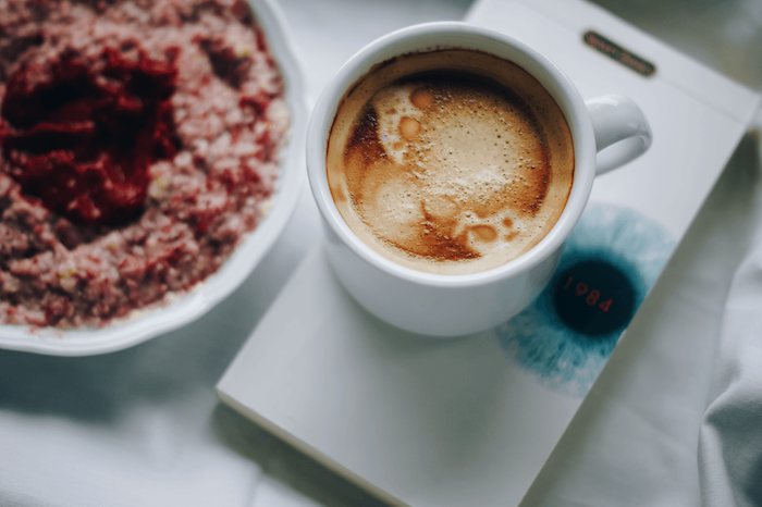 eine kleine Tasse Kaffee mit Milch auf einer weiße Untersilie und ein Kuchen - Guten Morgen Kaffee