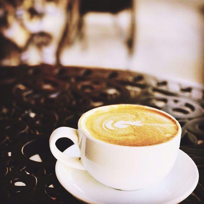 Guten Morgen Kaffee - eine Tasse mit Herzchen bemalt auf einem Tisch aus Metal