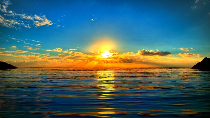 Guten Morgen Grüße - ein Sonnenaufgang über das Wasser mit kleinen Wolken