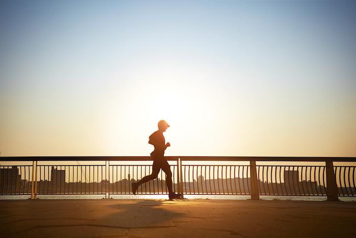 Guten Morgen Grüße - ein Mann joggt die Brücke entlang früh am Morgen