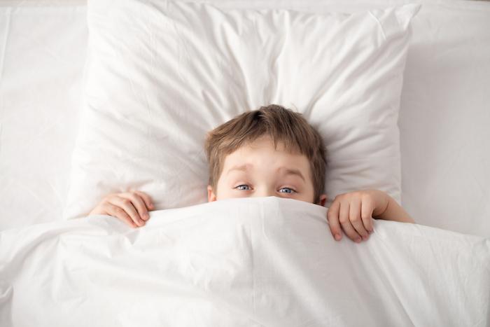 einen wunderschönen Guten Morgen - ein Junge versteckt sich unter die Decke