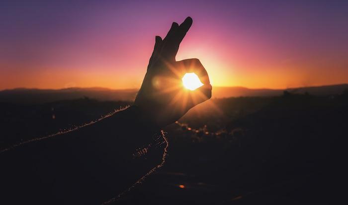 einen wunderschönen Guten Morgen - eine Hand hat den Sonnenaufgang gefangen