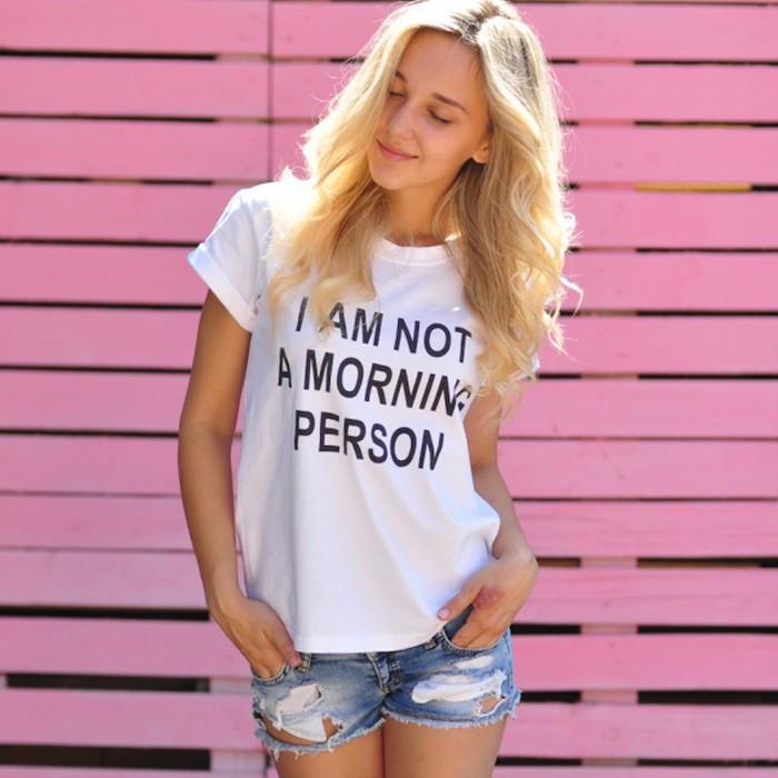 das Mädchen hat eine lustige Aufschrift auf dem T-Shirt - einen wunderschönen Guten Morgen