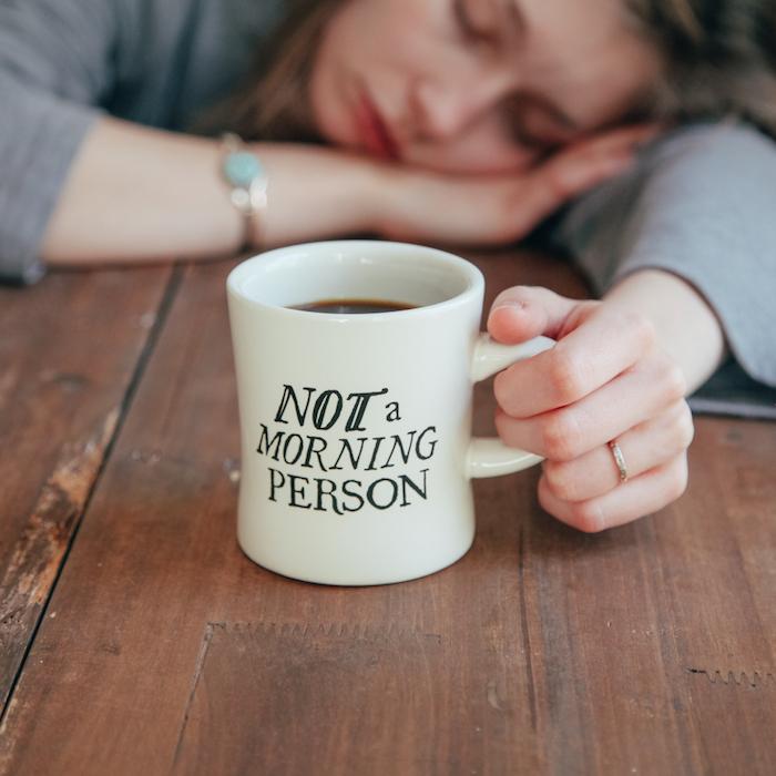 ein Kaffeebecher mit einer lustigen Aufschrift und eingeschlafenes Mädchen - einen wunderschönen Guten Morgen