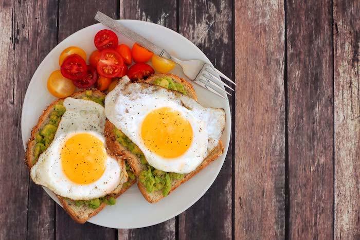 Guten Morgen Wünsche - Spiegeleier und Avocado Toast und Cherrytomaten