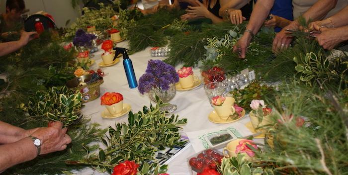 einige hände mit ästen mit grünen blättern und roten blumen - einen adventskranz binden