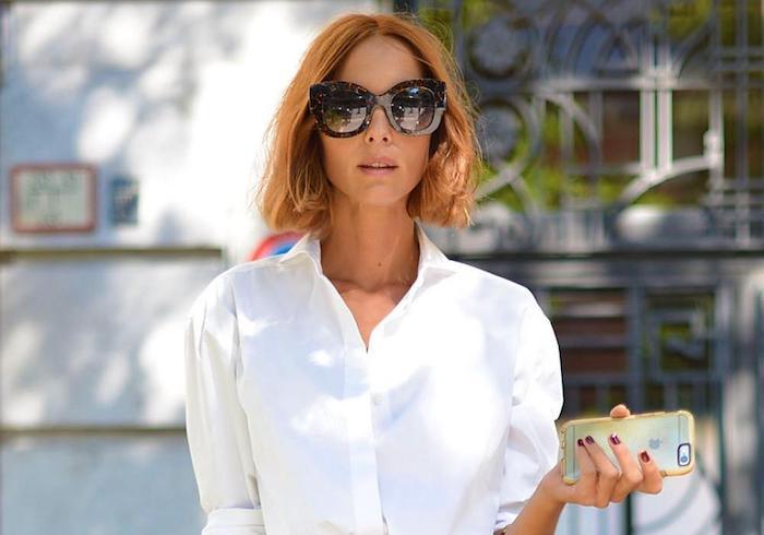 frau mit honigfarbene haare, großen sonnenbrillen und weißem hemd
