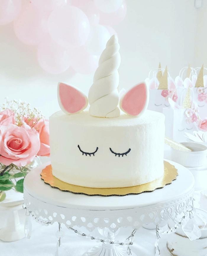 eine pinke rose und eine weiße torte mit einem langen weißen horn und mit pinken ohren und schwarzen augen - idee für einhorn kuchen