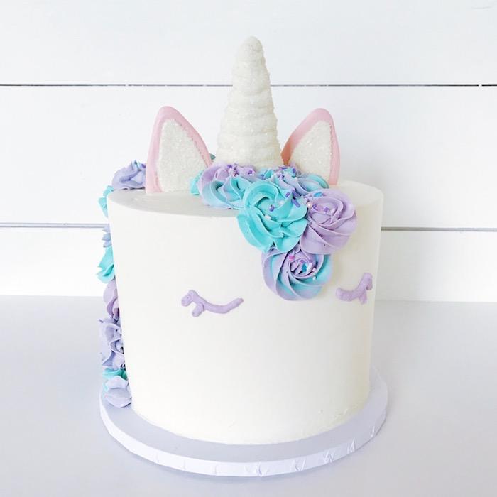 ein einhorn mit kleinen weißen ohren und lila augen und einem weißen horn und einer mähne aus sahne aus blauen und lila rosen