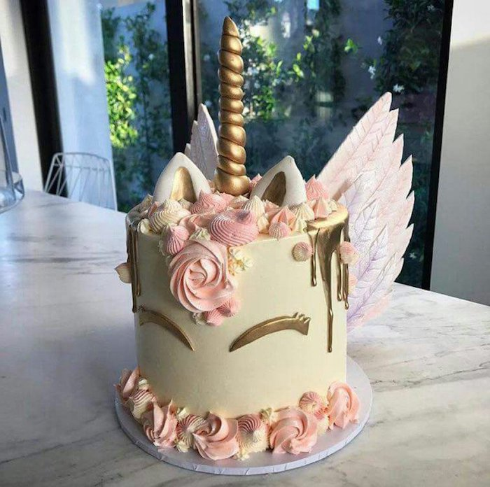 eine torte mit einem einhorn mit einem langen goldenen gelben horn und mit kleinen weißen ohren, pinken rosen aus sahne und pinken flügeln - idee für einhorn kuchen deko