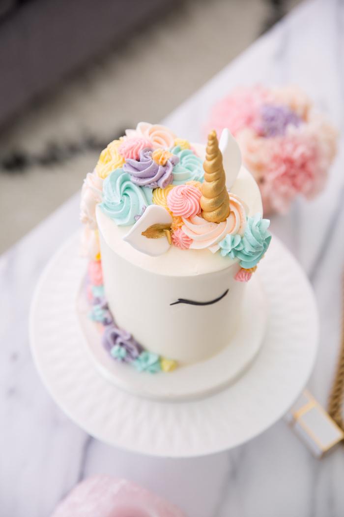 eine weiße torte mit einem weißen einhorn mit schwarzen augen und mit einer langen mähne mit pinken und lila rosen und einem goldenen gelben horn und schwarzen augen