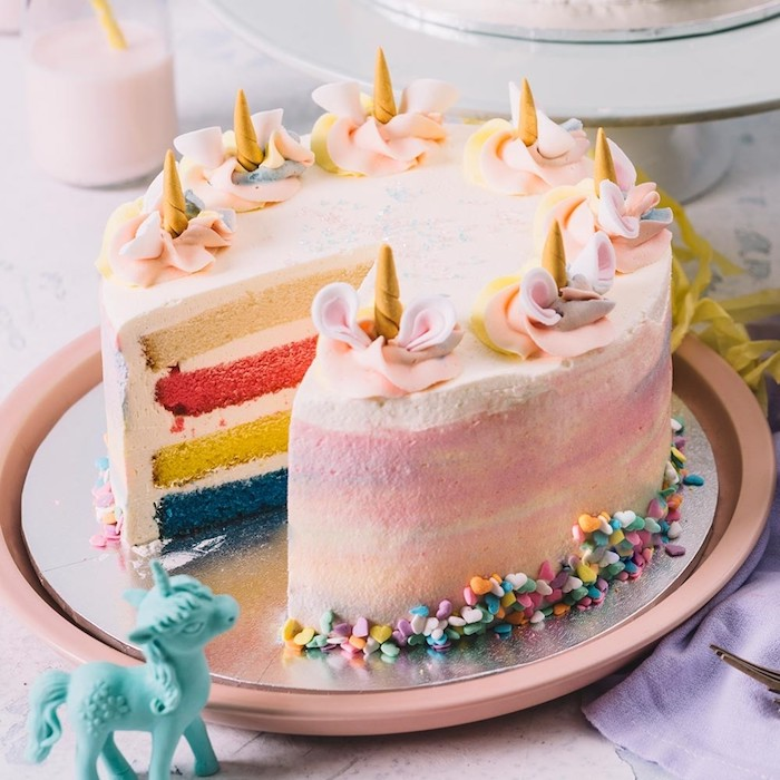 hier ist eine idee für eine pinke torte mit kleinen goldenen gelben hörnern und pinken ohren - regenbogenfarbene einhorn torte und ein kleines blaues einhorn - idee für einhorn kuchen deko