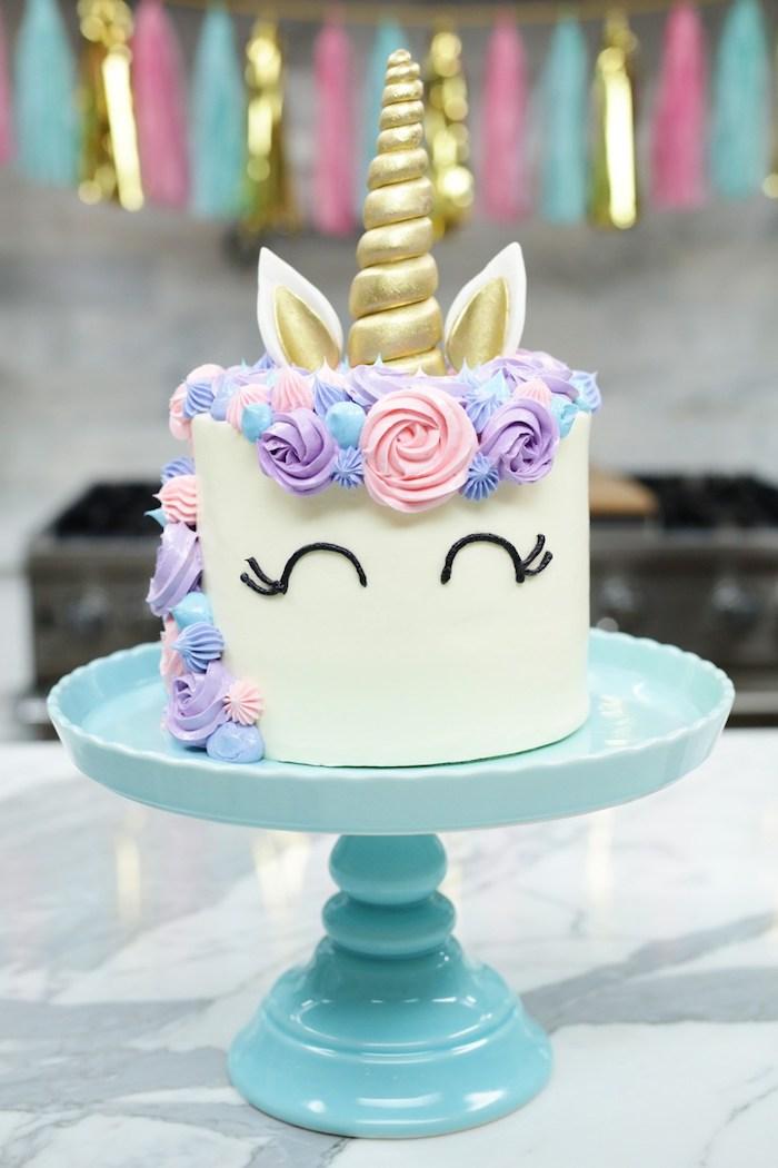 hier ist eine weiße einhorn torte mit einem weißen einhorn mit schwarzen augen und mit einer langen mähne mit pinken und lila rosen und einem goldenen langen horn - einhorn torte anleitung
